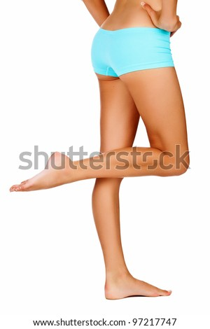 back of young tanned woman with beautiful sporty body and slim waistline - isolated on white wearing blue shorts style underwear - stock photo
