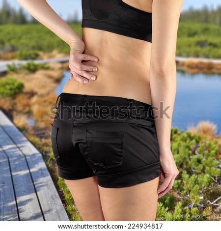 Back pain. Athletic woman in black sportswear standing and rubbing the muscles of her lower back, cropped torso. - stock photo