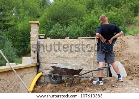 back pain, bricklayer builds a wall - stock photo