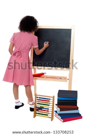 Back pose of a school girl finding solution and solving problems in maths class. - stock photo