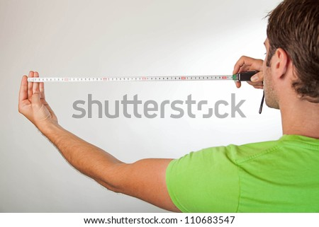back shot of a caucasian male measuring against a light background - stock photo