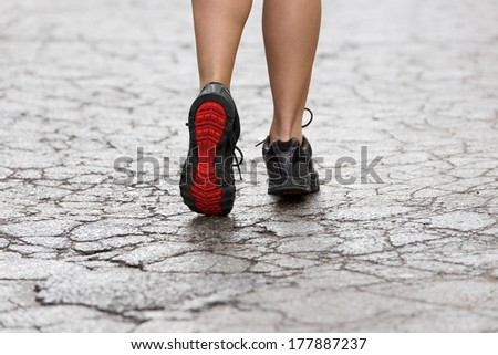 back shot of young lady with fitness shoes in act to walking ,running on a broken fashion road. USED SHOES  - stock photo