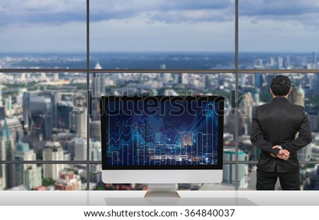 Back side of Businessman looking at citiy out off windows glass with Computer show Trading graph on the cityscape and world map background on the table in meeting room,Business financial concept - stock photo