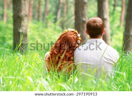 Back side of cute peaceful couple sitting on grass in the park, relaxing outdoors, enjoying romantic date  - stock photo