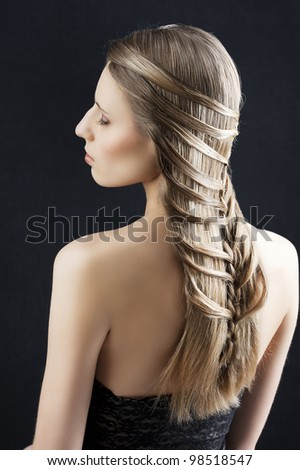 back side portrait of a fashion woman with long hair and old style and creative hairstylish, she is turned at her left with closed eyes - stock photo