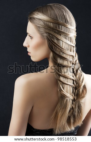 back side portrait of a fashion woman with long hair and old style and creative hairstylish, she is turned at her left and looks at left - stock photo