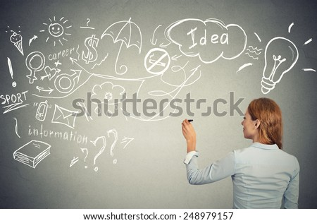 Back side view business woman writing with pen many ideas on grey wall blackboard planning future. Perception vision priorities career personal life balance concept. Decision making process concept. - stock photo