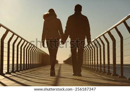 Back silhouette of a couple walking holding hands on a bridge in the beach at sunset - stock photo
