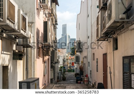 Back street of Tanjong Pagar historic  district in Singapore with modern skyscrapers  on the background as contrast to historic buildings. City architecture contrast, eclecticism - stock photo