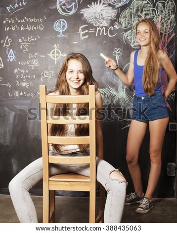 back to school after summer vacations, two teen real girls in classroom with blackboard painted together - stock photo