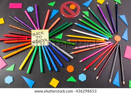 "Back to school background with a lot of colorful felt-tip pens and colorful pencils in circles and  title ""Back to school"" written on the yellow piece of paper on the black school chalkboard - stock photo"