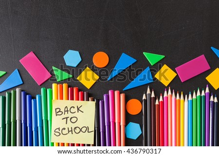 "Back to school background with a lot of colorful felt-tip pens and colorful pencils in row and  title ""Back to school"" written on the yellow piece of paper on the black school chalkboard - stock photo"