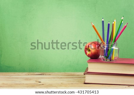 Back to school background with books, color pencils and apple over green wallpaper - stock photo