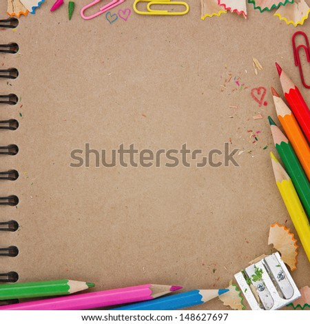 Back to school background with brown recycled paper notebook and colorful wooden pencils - stock photo