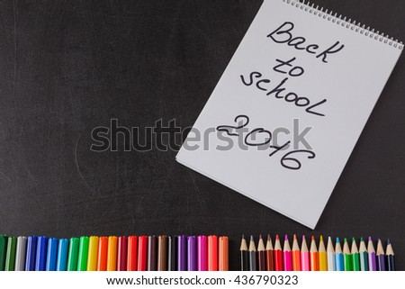 "Back to school background with colorful felt tip pens, pencils and the  notebook with title ""Back to school 2016"" on the black school chalkboard - stock photo"
