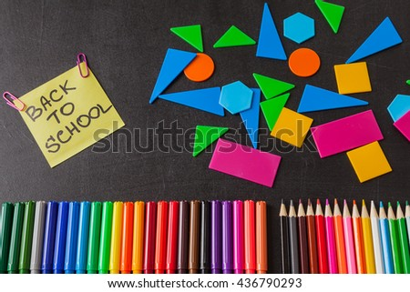 "Back to school background with colorful felt tip pens, pencils, geometric figures and  title ""Back to school"" written on yellow piece of paper on the black school chalkboard - stock photo"