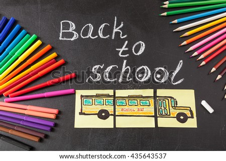 "Back to school background with colorful felt tip pens, pencils,  title ""Back to school"" written by white chalk and the school bus drawn on yellow pieces of paper on the black school chalkboard - stock photo"
