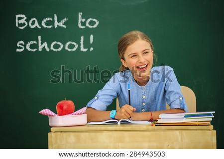 Back to school - beautiful schoolgirl in the classroom - stock photo