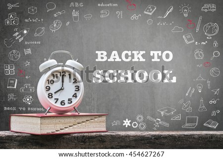 Back to school: Black chalkboard background for announcement w/ wake up alarm clock & textbook on grunge old dark wood top doodle graphic: Students' educational time for learning system concept - stock photo