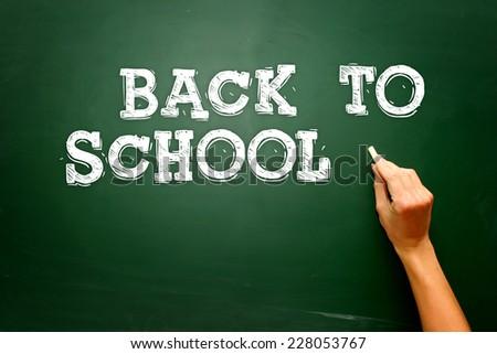 Back to school blackboard / chalkboard. Teacher writing back to school on black chalk board - stock photo