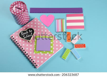 Back to School bright pink, polka dot and colorful stationery and office supplies with money savings box on pale blue background. - stock photo