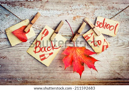 Back to school card with autumn leaf on wooden background - stock photo