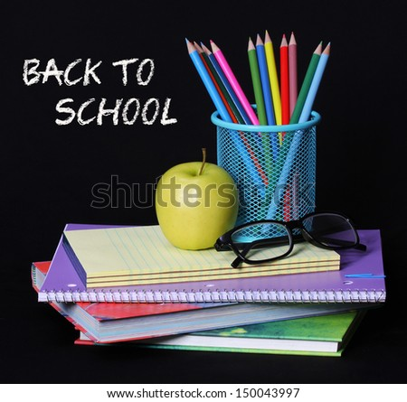 Back to school concept. An apple, colored pencils and glasses on pile of books over black background . The words 'Back to School' written in chalk on the blackboard   - stock photo