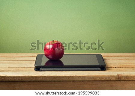 Back to school concept. Apple and tablet device on wooden table - stock photo