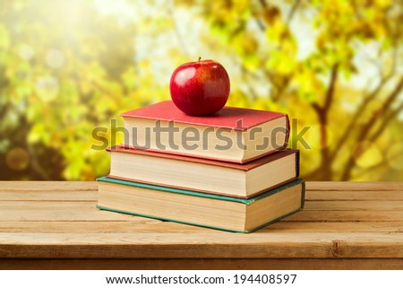 Back to school concept. Apple on old books over autumn trees background - stock photo