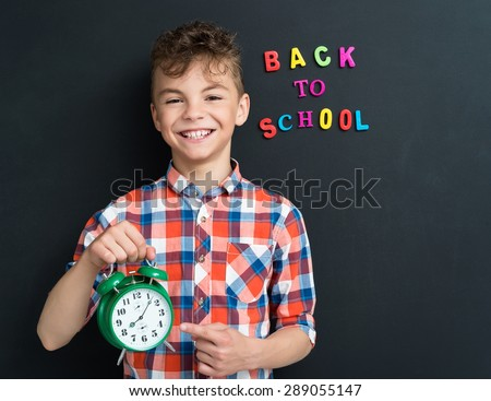 Back to school concept. Boy with big green alarm clock at the black chalkboard in classroom. - stock photo