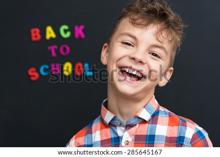 Back to school concept. Cheerful schoolboy at the black chalkboard in classroom. - stock photo