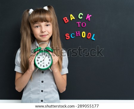 Back to school concept. Girl with big green alarm clock at the black chalkboard in classroom. - stock photo