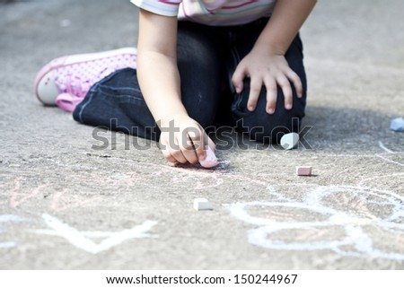 Back to school concept -Photo of girl writing with chalk on the schoolyard  - stock photo
