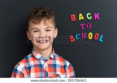 Back to school concept. Portrait of a schoolboy at the black chalkboard. - stock photo