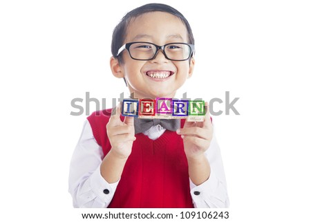 Back to school concept; Portrait of asian elementary school student showing letter blocks spelling out LEARN. Shot in studio isolated on white - stock photo