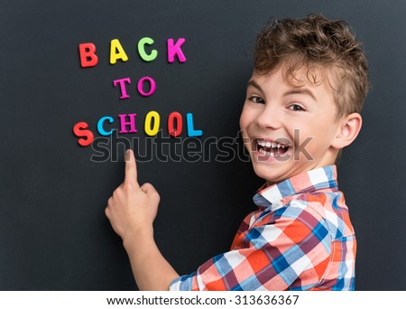 Back to school concept. Portrait of happy pupil at the black chalkboard. - stock photo