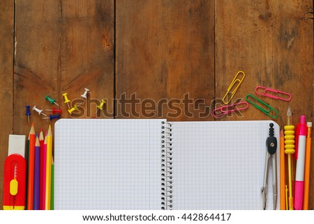Back to school concept. School supplies on wooden desk with empty open notebook for copy space - stock photo