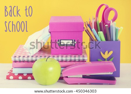 Back to School Concept with classroom desk and bright colored stationery supplies on white wood rustic table and fun yellow background, with added filters and retro hand drawn style text.  - stock photo