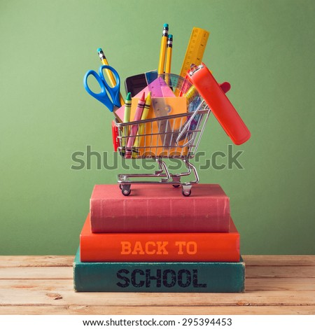 Back to school concept with shopping cart on books - stock photo