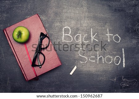 back to school concept with various staff on blackboard background - stock photo