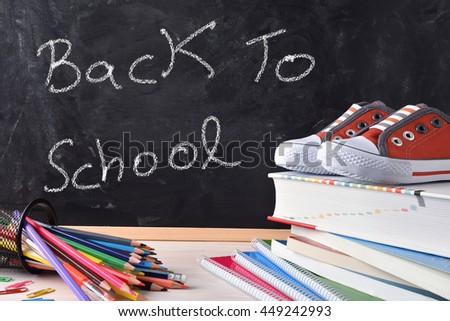 Back to school concept written with chalk on a blackboard and school supplies and sneakers. Front view - stock photo