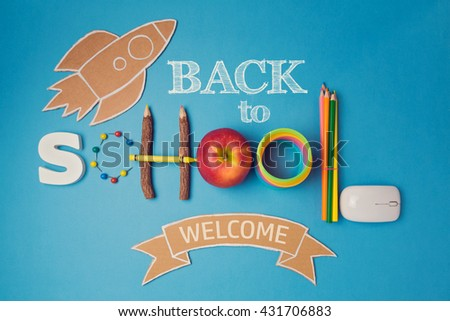 Back to school creative design with apple, school supplies and cardboard rocket. View from above - stock photo
