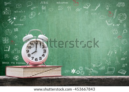 Back to school: Green chalkboard background for announcement w/ wake up alarm clock & textbook on grunge old dark wood top doodle graphic: Students' educational time for learning system concept - stock photo