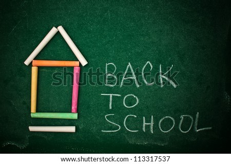 Back to school, handwritten letters on a green chalkboard. Colorful chalks forming the shape of a house or a school building. - stock photo