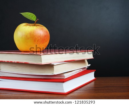 Back to school. Image of teacher's desk with a pile of textbooks and apple - stock photo