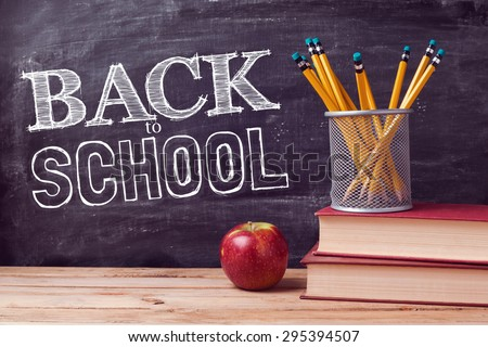 Back to school lettering with books, pencils and apple over chalkboard background - stock photo