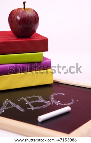 Back to school letters written on a blackboard with colorful books (selective focus) - stock photo