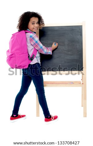 Back to school - little schoolgirl writing on blackboard, space for text. - stock photo