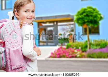 Back to school - lovely schoolgirl on the way to the school - stock photo