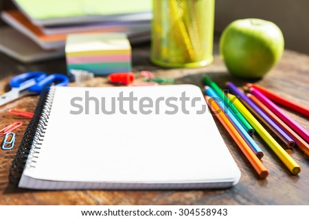 Back to school: note book, pencils, loupe, green apple on wooden table - stock photo